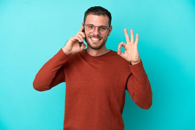 Junge brasilianische mann mit handy isoliert auf blauem hintergrund zeigt ok zeichen mit den fingern