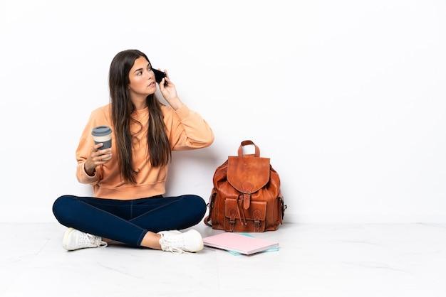 Junge brasilianische studentin sitzt auf dem boden und hält kaffee zum mitnehmen und ein handy