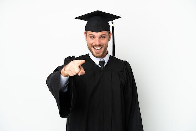 Junge brasilianische universitätsabsolventin isoliert auf weißem hintergrund überrascht und zeigt nach vorne Premium Fotos