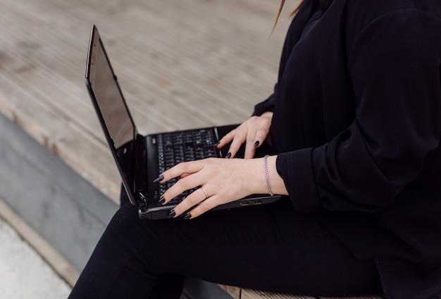 Junge braune haarfrau mit laptop und smartphone-computer, der auf holzboden sitzt