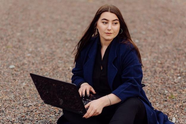 Junge braune haarfrau mit laptop und smartphone-computer, der auf steinen sitzt
