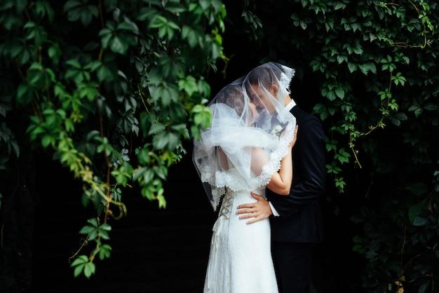 Junge braut, die ihren bräutigam im schönen park umarmt