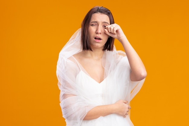 Junge braut im schönen hochzeitskleid, das müde und gelangweilte augen reibt, die über orangefarbener wand stehen