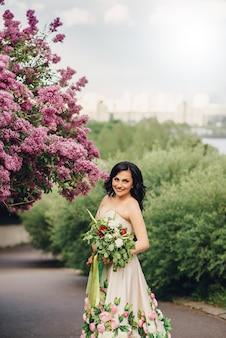 Junge braut in einem luxuriösen blumenkleid steht in einem blühenden lila garten