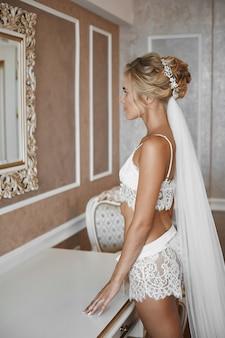 Junge braut mit schlankem körper und platinblondem haar, das nahe dem spiegel im weinleseinnenraum aufwirft. blondes modellmädchen mit schlankem körper und brautfrisur in spitzenwäsche, die im innenraum aufwirft.
