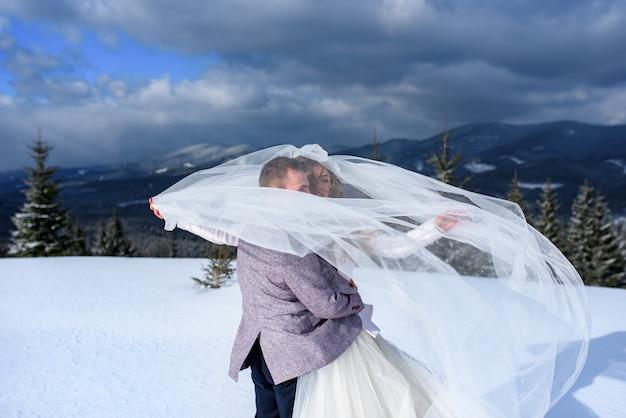 Junge braut und bräutigam auf dem schneebedeckten berg