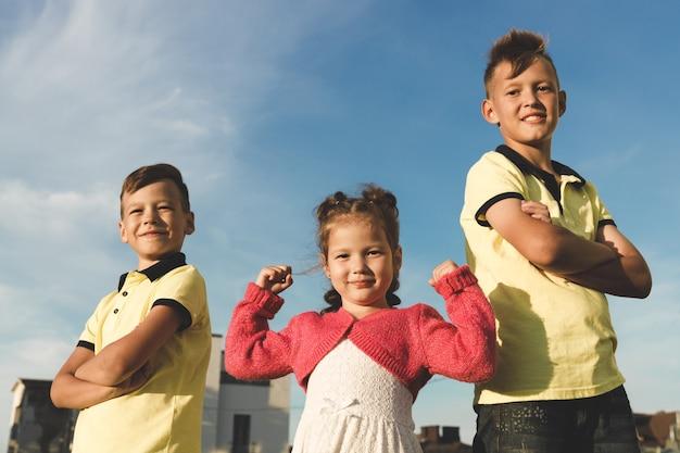 Junge brüder in gelben t-shirts und eine schwester, die muskeln in ihren armen zeigt. im sommer draußen. gegen den himmel