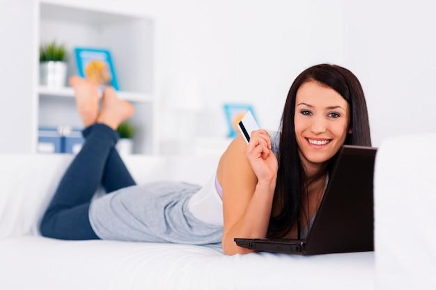 Junge brünette, die auf der couch mit einer kreditkarte und einem laptop liegt