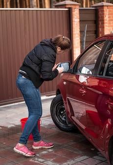 Junge brünette frau, die autospiegel wäscht