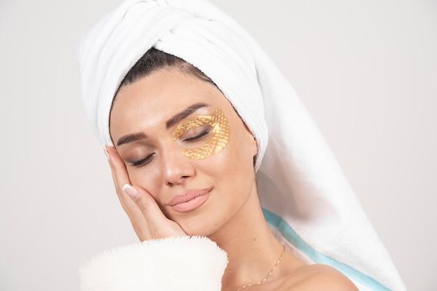 Junge brünette frau, die bademantel mit kosmetischen augenklappen trägt