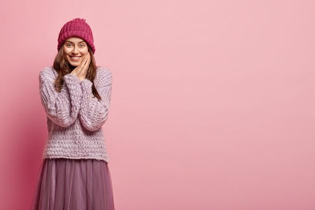 Junge brünette frau, die bunte winterkleidung trägt
