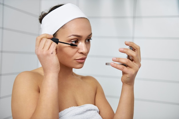 Junge brünette frau, die einen kosmetischen spiegel einerseits und wimperntusche andererseits hält. frau, die wimperntusche auf ihren wimpern anwendet und einen spiegel betrachtet.