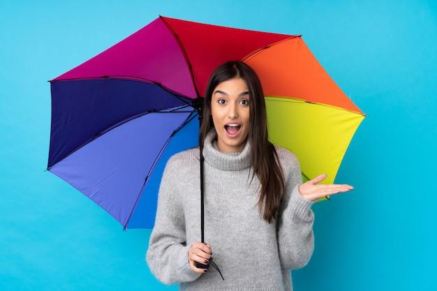 Junge brünette frau, die einen regenschirm über isolierter blauer wand mit überraschendem gesichtsausdruck hält