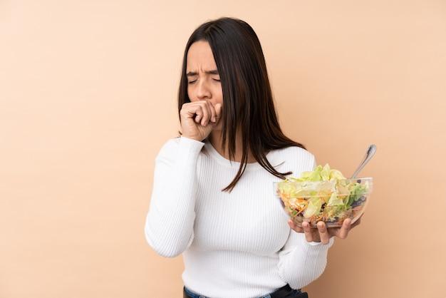 Junge brünette frau, die einen salat hält, leidet unter husten und fühlt sich schlecht