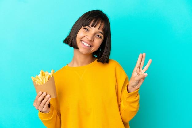 Junge brünette frau, die gebratene chips über isoliertem blauem hintergrund hält, glücklich und zählt drei mit den fingern