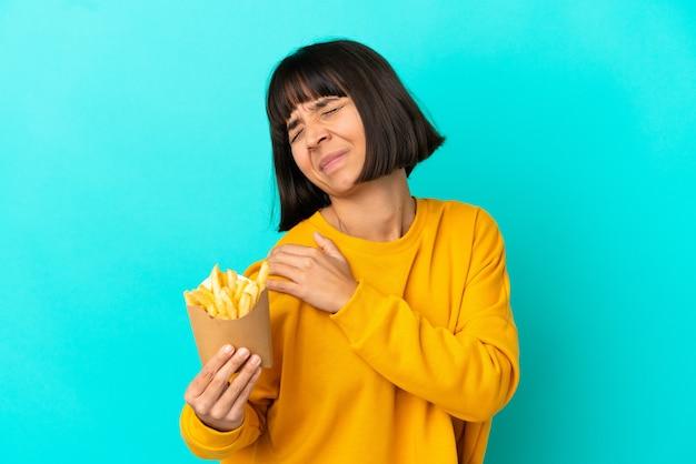 Junge brünette frau, die gebratene chips über isoliertem blauem hintergrund hält und unter schmerzen in der schulter leidet, weil sie sich angestrengt hat?