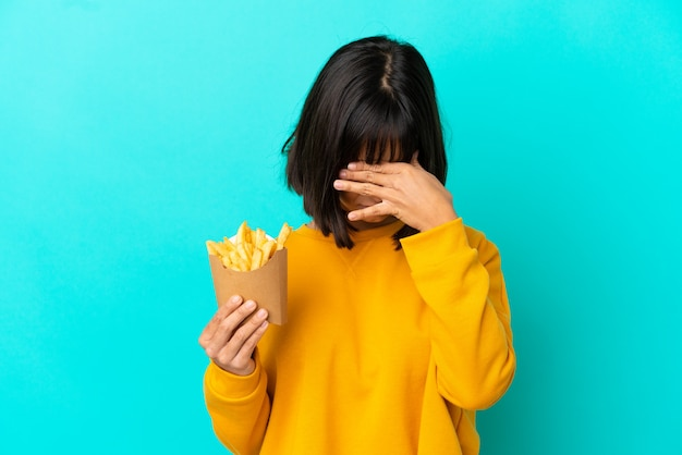 Junge brünette frau, die gebratene chips über isoliertem blauem hintergrund mit müdem und krankem gesichtsausdruck hält