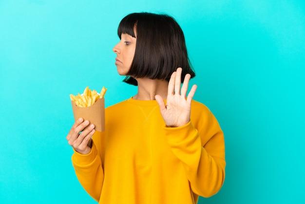 Junge brünette frau, die gebratene chips über isolierter blauer oberfläche hält, stop-geste macht und enttäuscht
