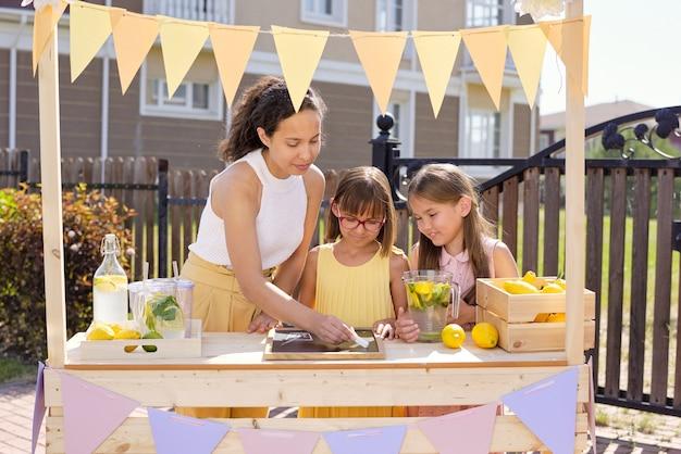 Junge brünette frau, die glas des getränks auf pinnwand mit kreide zeichnet, während ihre töchter nahe stehen und limonade durch stall verkaufen