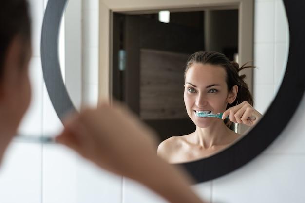 Junge brünette frau, die ihre zähne vor badezimmerspiegel putzt