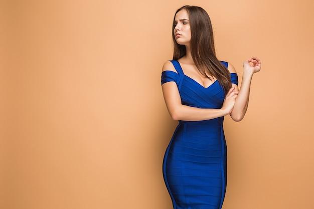 Junge brünette frau, die in einem blauen kleid auf braunem hintergrund aufwirft