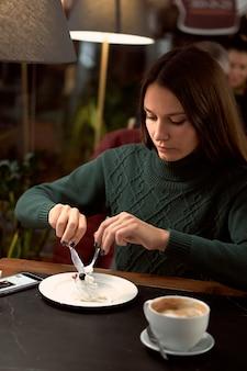 Junge brünette frau, die kaffee in einem café trinkt und nachtisch isst