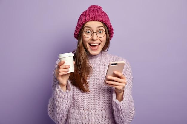 Junge brünette frau, die lila pullover trägt und tasse kaffee hält