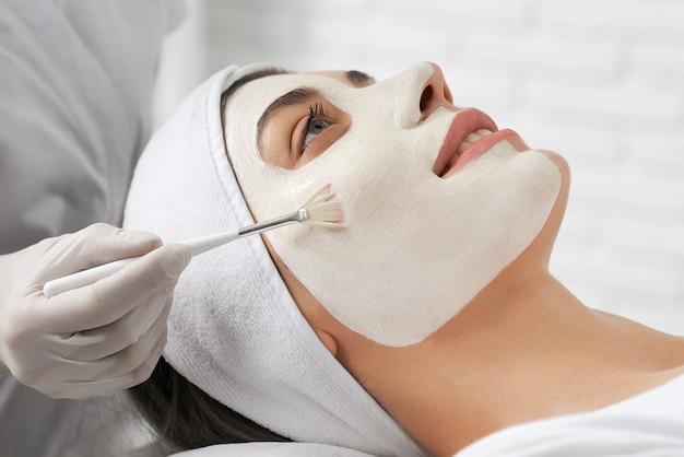 Junge brünette frau, die maske in kosmetikerin tut