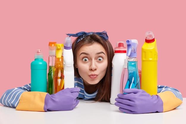 Junge brünette frau, die neben reinigungsprodukten sitzt