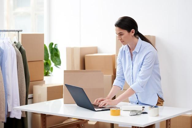 Junge brünette frau, die neue bestellungen vor laptop beim bücken über schreibtisch im online-shop-büro nimmt
