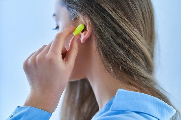 Junge brünette frau, die ohrstöpsel für lärmschutz verwendet