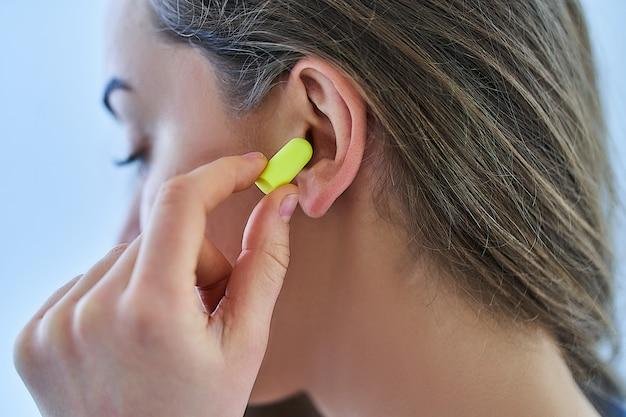 Junge brünette frau, die ohrstöpsel für lärmschutz zu hause verwendet
