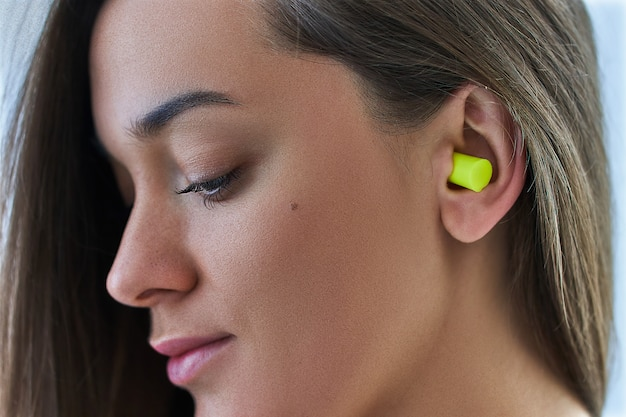 Junge brünette frau, die ohrstöpsel für lauten lärmschutz verwendet