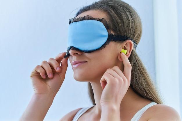 Junge brünette frau, die ohrstöpsel und augenmaske für besseren schlaf und süße träume verwendet