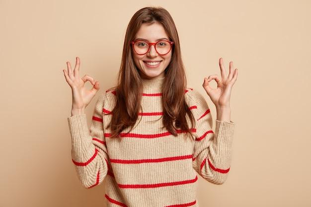 Junge brünette frau, die rote brillen trägt