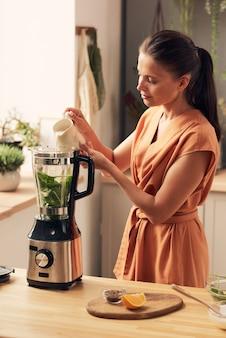Junge brünette frau, die spinat-smoothie am küchentisch zubereitet