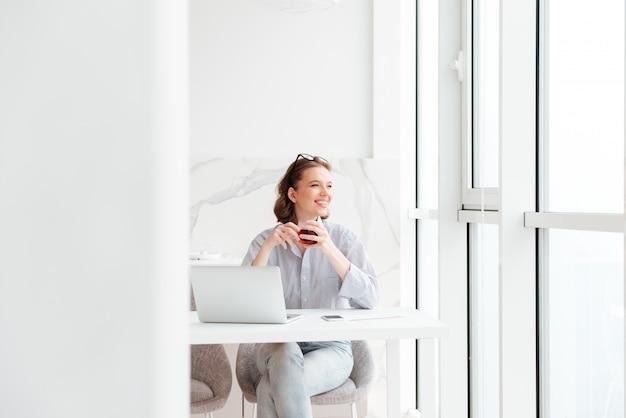 Junge brünette frau, die tasse tee hält, während sie an der küche sitzt und großes fenster betrachtet