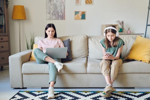 Junge brünette frau, die während des netzwerks auf laptop-display schaut, während ihre süße tochter im teenageralter in kopfhörern in der nähe auf dem smartphone scrollt