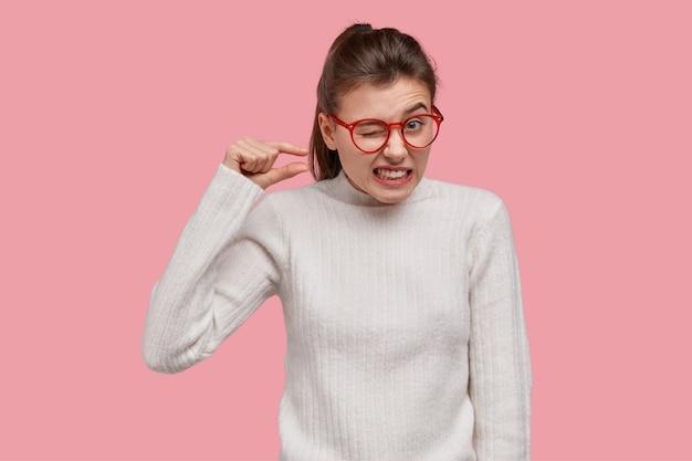Junge brünette frau, die weißen pullover und rote brille trägt