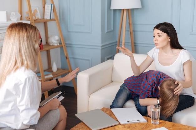 Junge brünette frau, die weißes t-shirt trägt, das ihre linke hand auf kopf ihres sohnes legt, während sie mit psychologe spricht