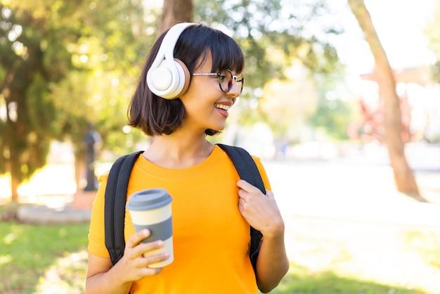 Junge brünette frau im freien, die musik hört und einen kaffee zum mitnehmen hält