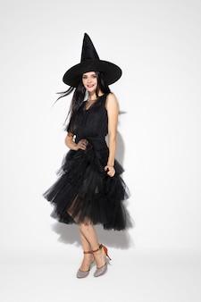 Junge brünette frau im schwarzen hut und im kostüm auf weißem hintergrund. attraktives kaukasisches weibliches modell. halloween, schwarzer freitag, cyber-montag, verkauf, herbstkonzept. copyspace. tanzen, posieren.