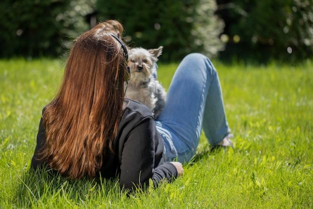 Junge brünette frau in den kopfhörern, die in der natur mit kleinem haustierhund erfreuen, der ansicht genießt, auf gras im park liegend