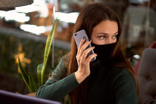 Junge brünette frau in der medizinischen maske im café mit laptop