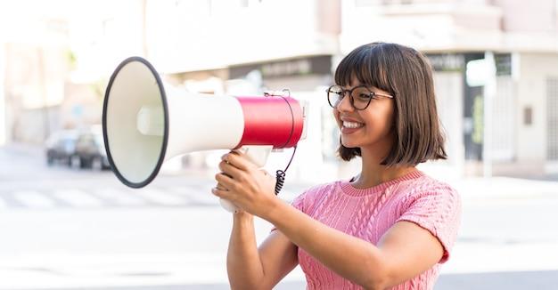 Junge brünette frau in der stadt, die durch ein megaphon schreit, um etwas anzukündigen