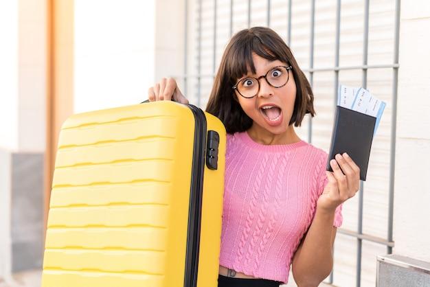 Junge brünette frau in der stadt im urlaub mit koffer und pass