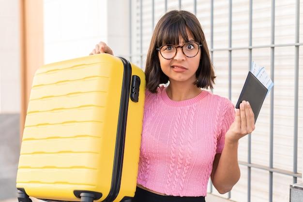Junge brünette frau in der stadt unglücklich im urlaub mit koffer und pass