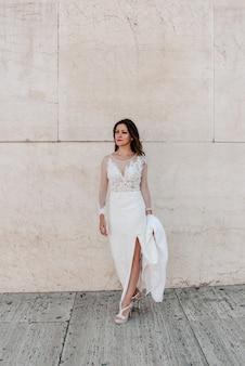 Junge brünette frau in einem hochzeitskleid mit einem marmorhintergrund