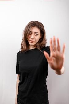 Junge brünette frau in einem schwarzen t-shirt auf weiß. negation isoliert