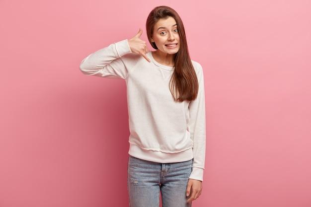 Junge brünette frau in jeans und pullover